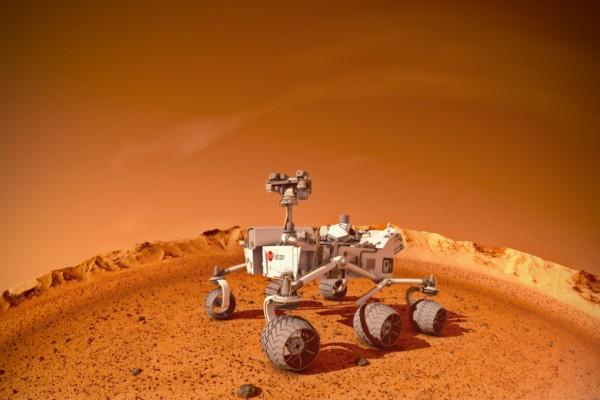 A Mars rover on a red dirt landscape.