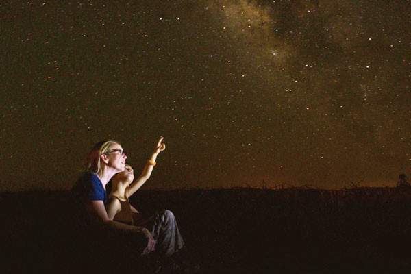 Mum and daughter pointing at a night sky full of stars.