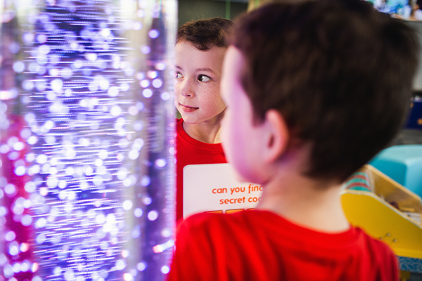 A young boy looking at a light display amused