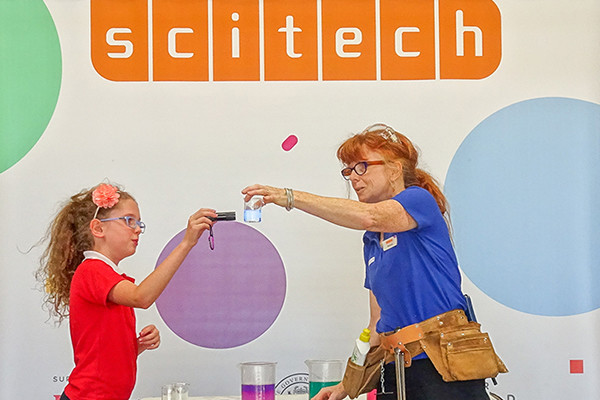 A Scitech Presenter holding a beaker of water while a young girl holds an electronic device to it.