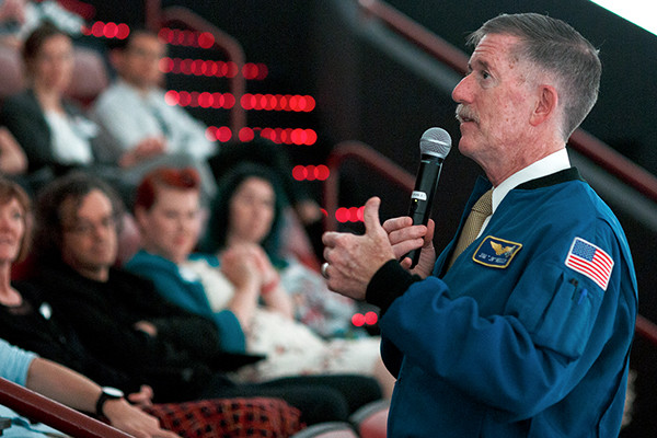 A man wearing an American flag and NASA jacket presenting a speech to a group of people.