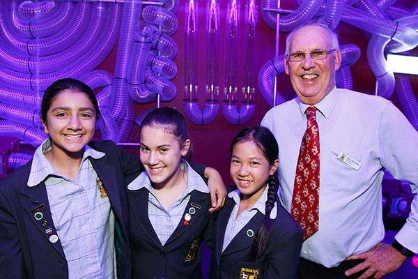 Three high school girls posing with a middle aged man at Scitech.