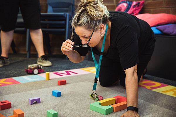 Teacher sitting on the ground looking at coloured blocks.