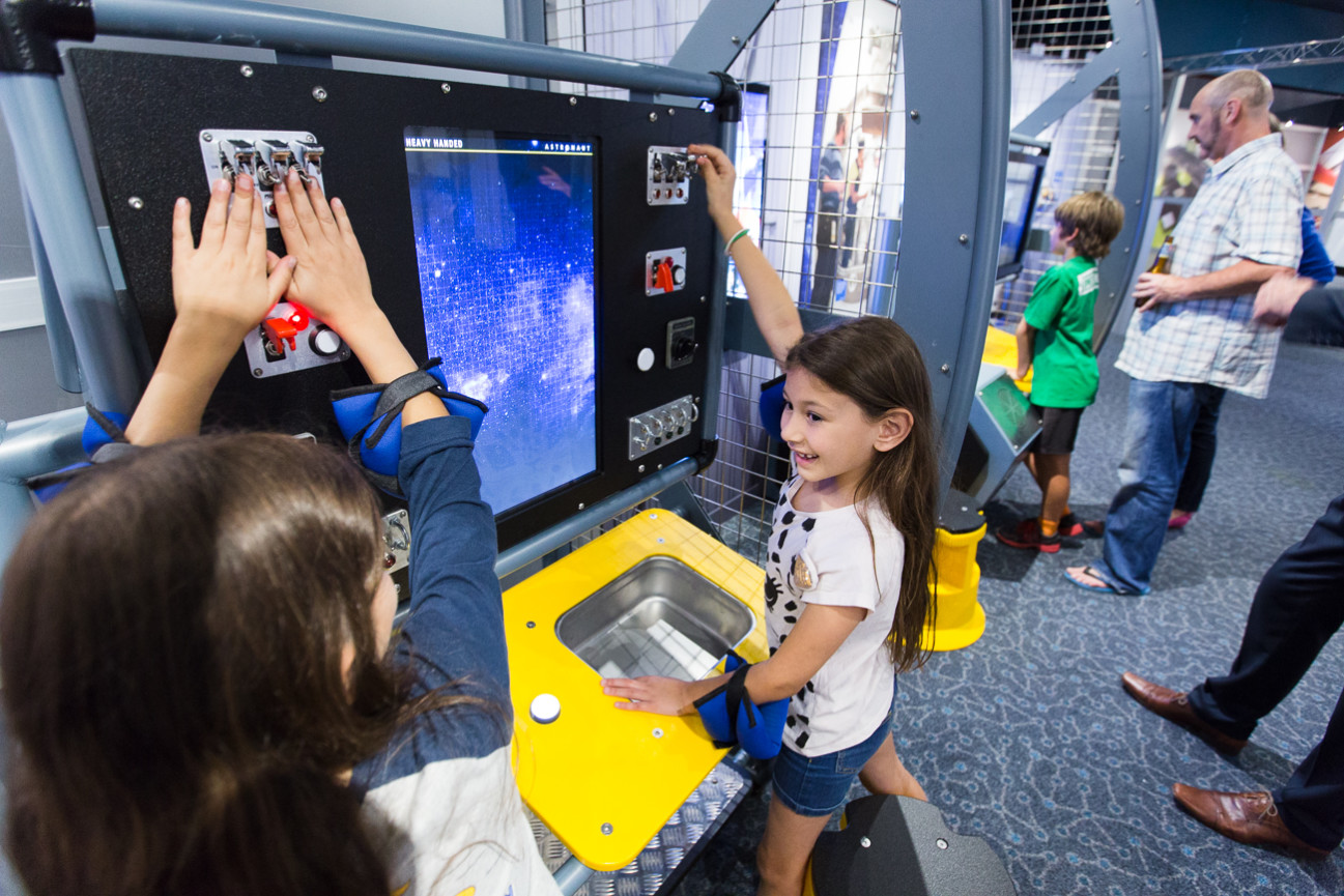 Two young girls playing with the astronaut exhibit at Scitech, pushing switches on a large panel