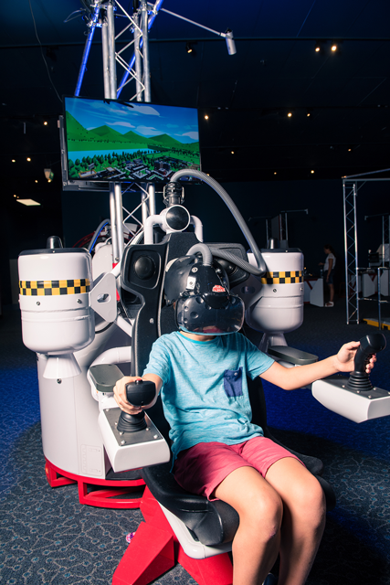 A young boy wearing a vr headset sitting in a jet pack simulator.