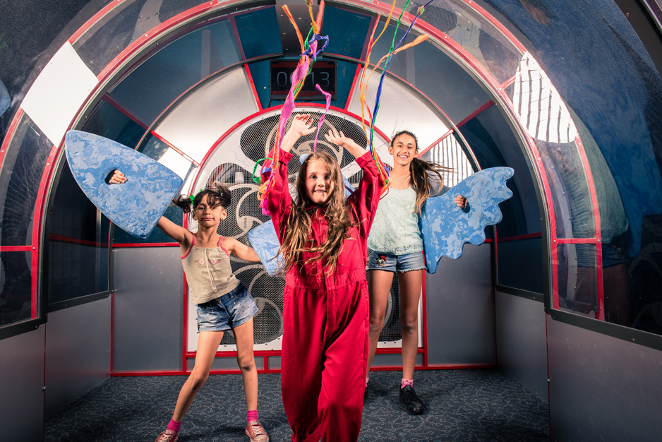 Three teenage girls in a wind tunnel exhibit holding streamers and wings.