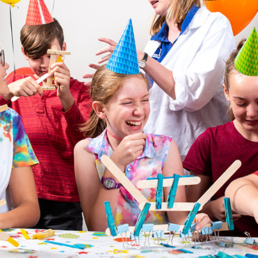 A group of children in birthday hats build objects out of wooden pop sticks and blue pegs