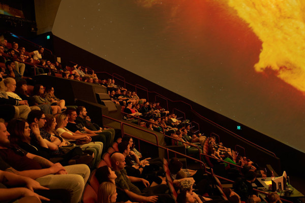 Adult audience watching a show in the planetarium.
