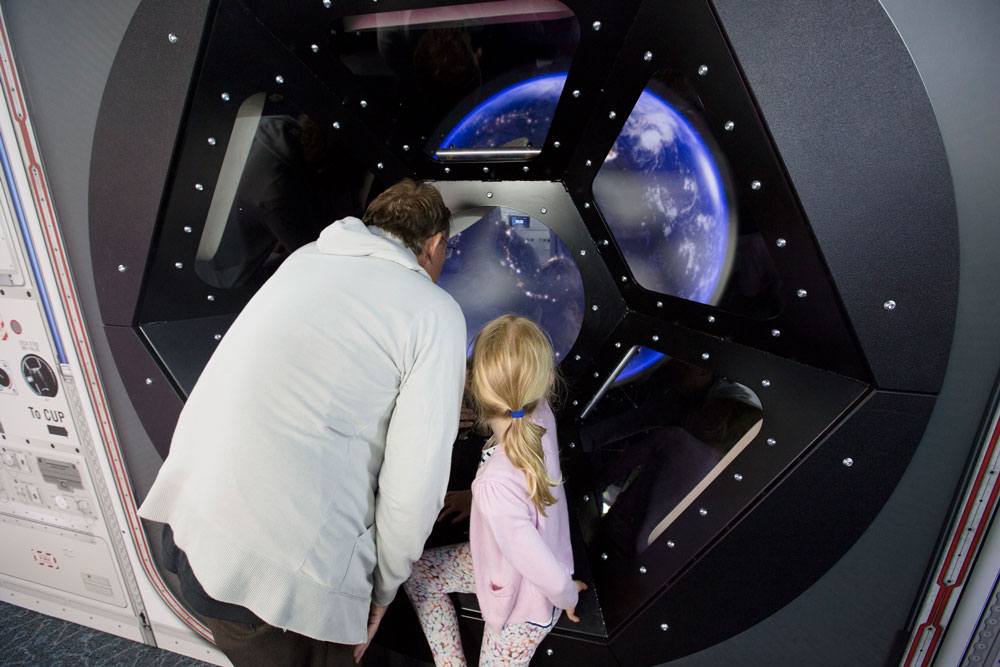 Parent and young girl looking into exhibit of the earth at Scitech.