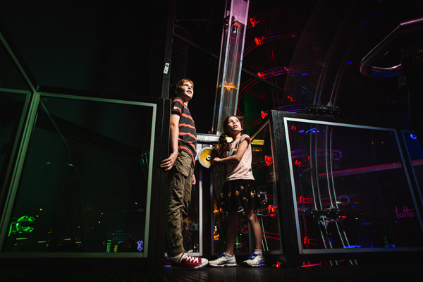 Two children looking up at coloured lights.