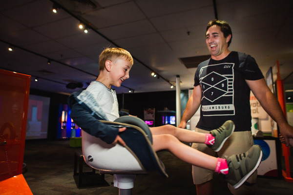 Young boy and adult man playing on spinning chair exhibit.