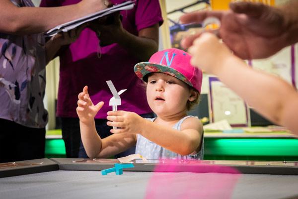 Little girl testing a folded paper flying object