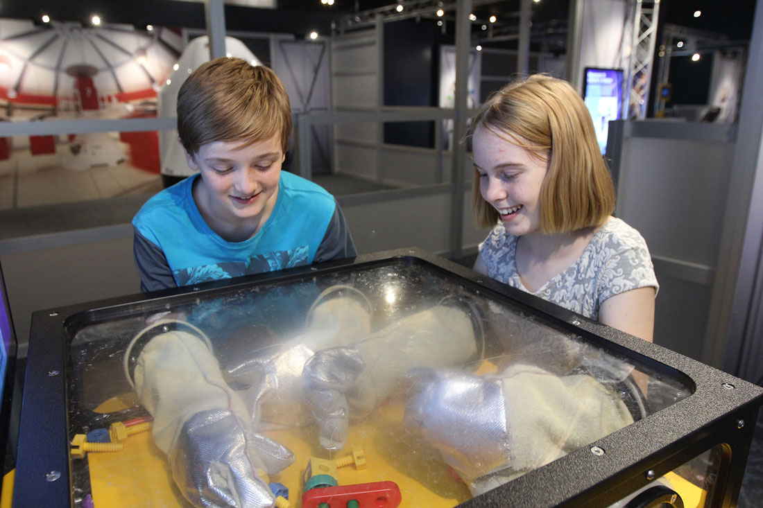 Two children putting their hands in space gloves trying to grab objects at the Astronaut exhibit in Scitech.
