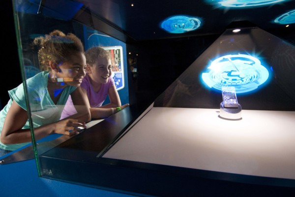 Two girls look at a holographic image being projected into a prism of glass