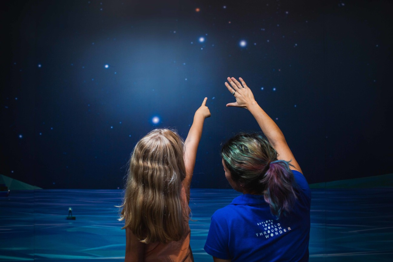 A young girl points to a star on a wall sized image of the night sky over the ocean, with a Scitech staff member guiding them
