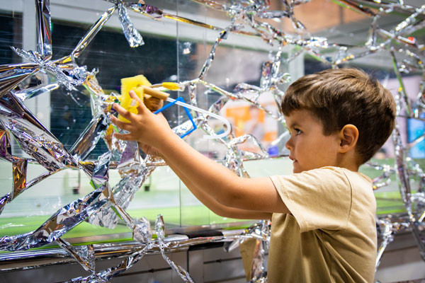 A toddlers experiments with a model spider on a shimmering web