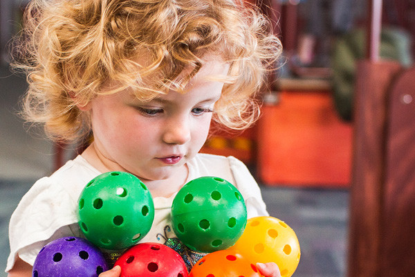 A toddler playing intently with colourful plastic balls