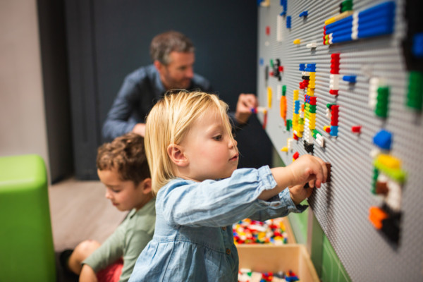 A young child places lego on the wall.