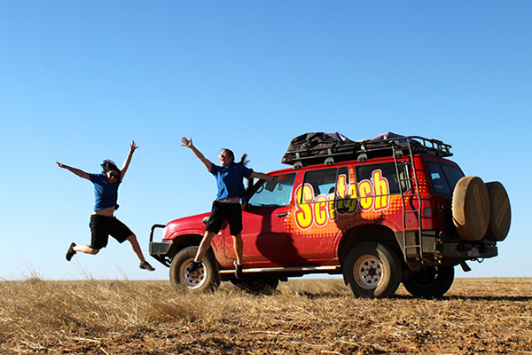Two scitech outreach staff jump into the air in front of a parked red Scitech branded four wheel drive in regional WA