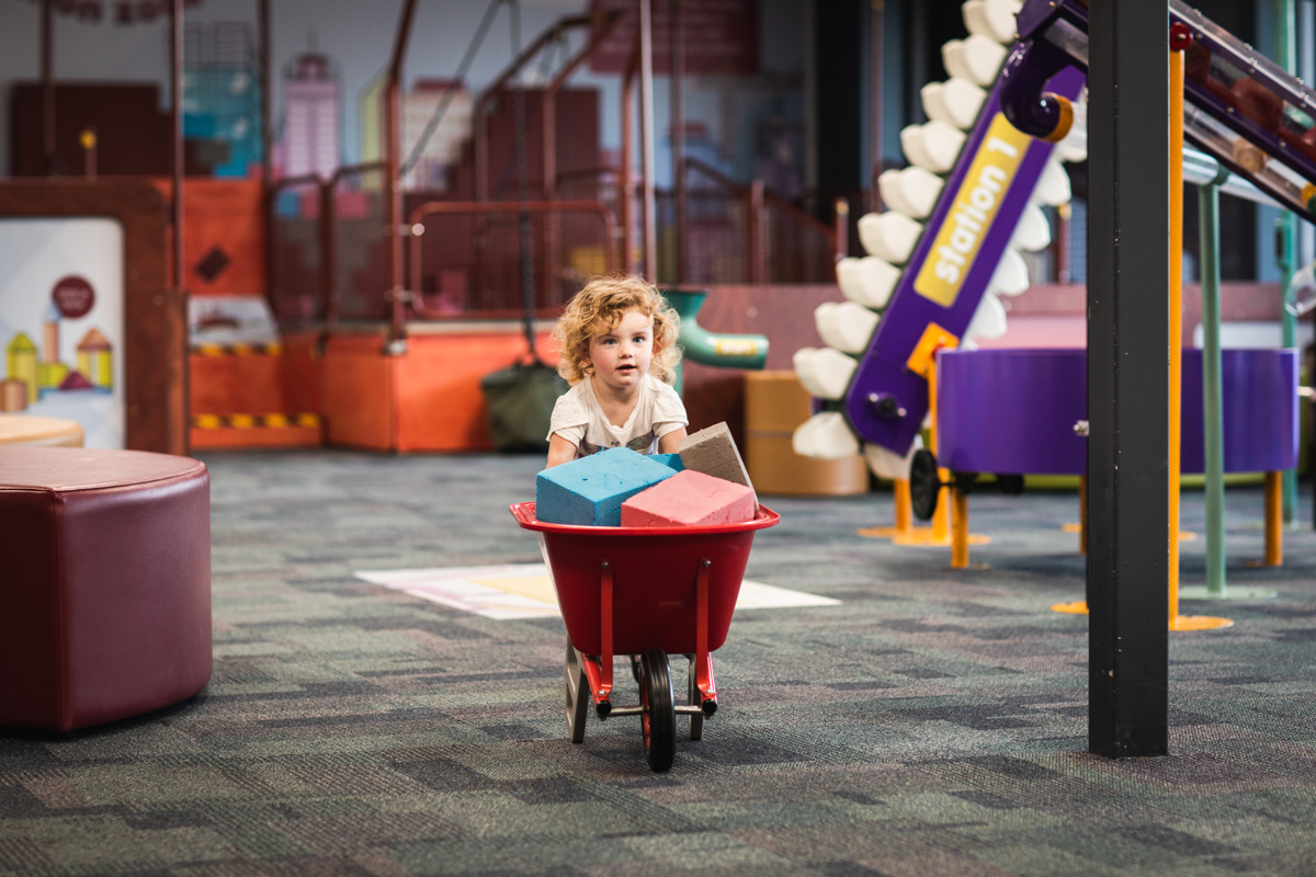 Young child pushing a wheelbarrow full of blocks in Discoverland.