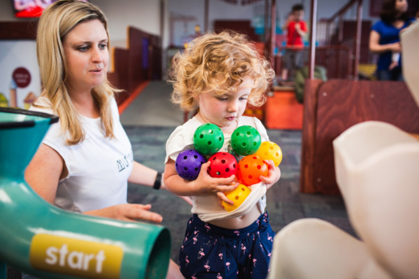 Young girl playing with coloured, plastic balls in Discoverland.