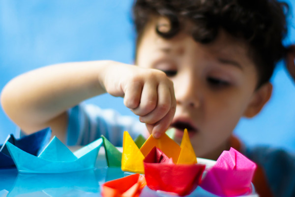 Young boy playing with origami boats in Discoverland.