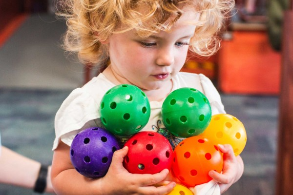 A young girl holding 7 coloured plastic balls
