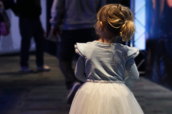 A young girl in a fairy outfit following a crowd of adults inside scitech