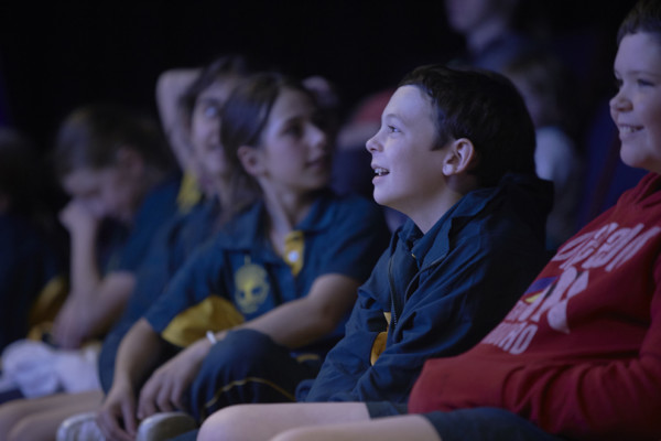 A group of school children are watching something while seated in the planetarium