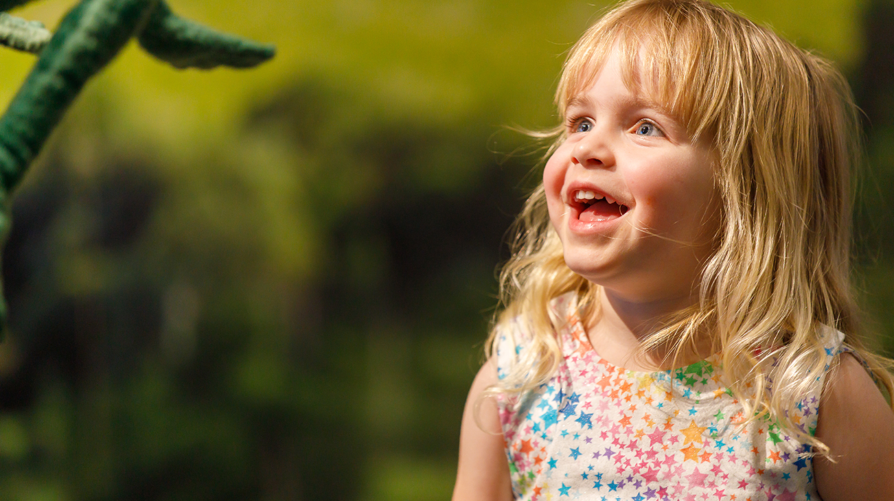 Young girl toddler looks up excitedly at lizard puppet