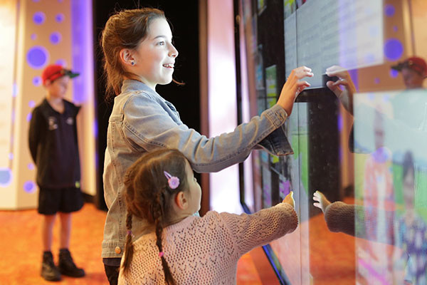 Two girls playing with a wall made of touchscreens