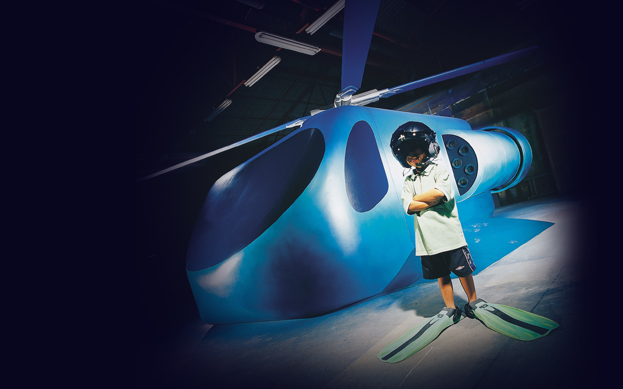 A young boy in a helicopter pilot helmet and flippers stands cross armed in front of a boxy helicopter shaped simulator