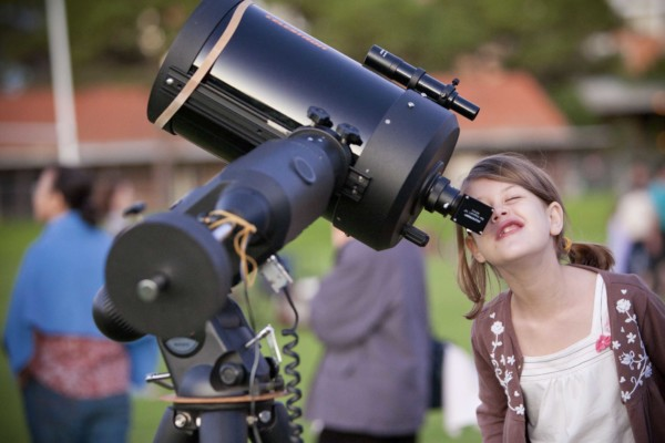 A young girl looks into the view finder of a large telescope outside.