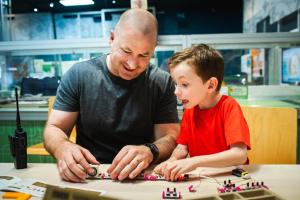 A man and a young boy piece together a series of circuit boards on a table