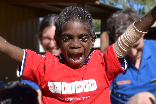 An indigenous child in a red scitech shirt has his arms up and is cheering