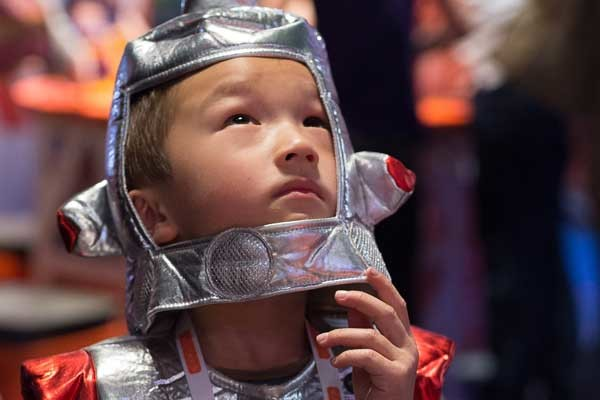 A young boy wearing a soft astronaut costume