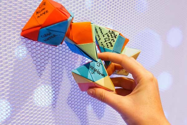 A series of colourful paper origami shapes, folded with writing on each side, attached to a white mesh wall, with a hand grabbing one of the items