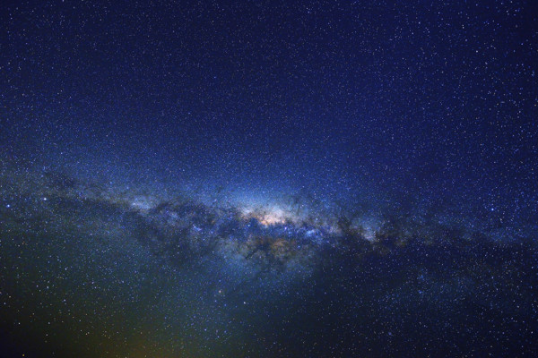 Photo of the night sky with the Milky Way stretching across it horizontally