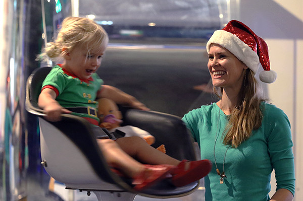 A young girl in an elf outfit with her toy baby sit in a spinning chair while a lady watches her, smiling