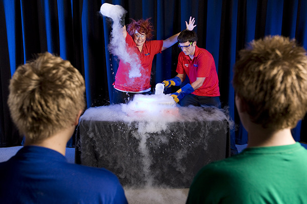 Two Scitech presenters pouring liquid ice into a bowl for a science show.