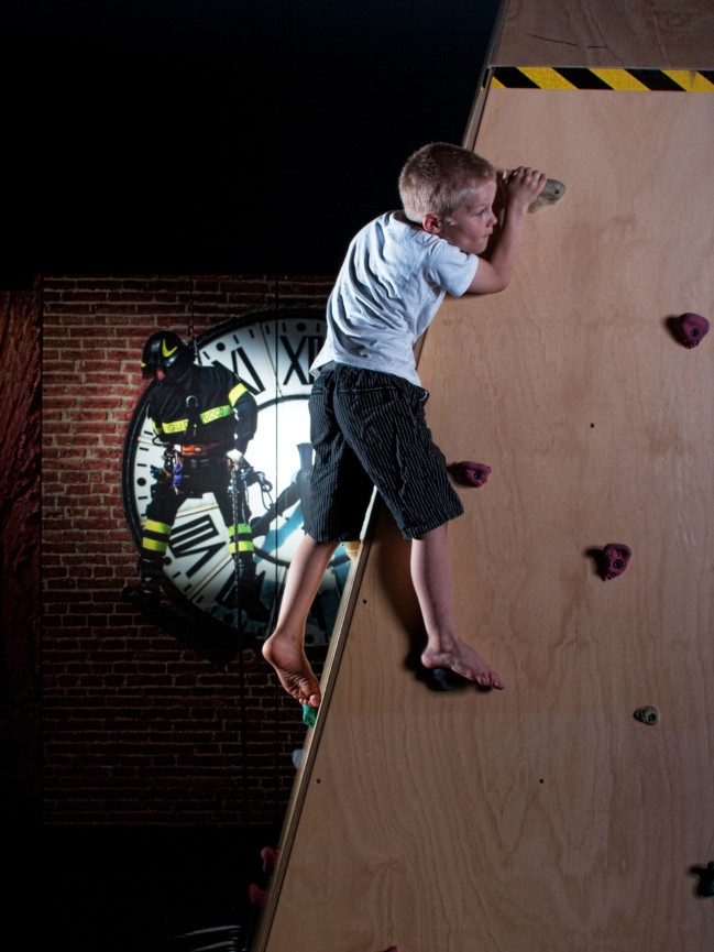 A young boy climbing on the Bouldering wall in the Rescue Exhibit.