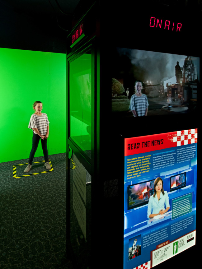 A young girl presenting a news segment in front of a green screen for the Rescue Exhibition.