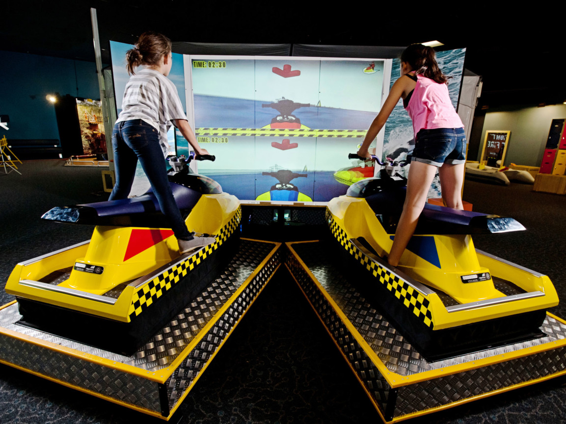 Two girls riding the jet ski simulator in the Rescue exhibit.