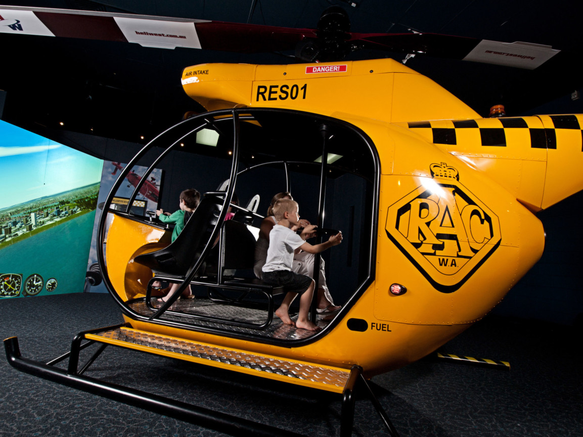 A group of children flying a helicopter simulation in the Rescue Exhibition at Scitech.