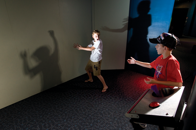Two boys playing hand puppets and facing each other in a room.