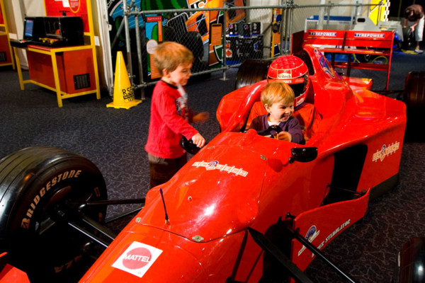 Two young boys playing in a formula one replica race car in Scitech's Speed exhibition.