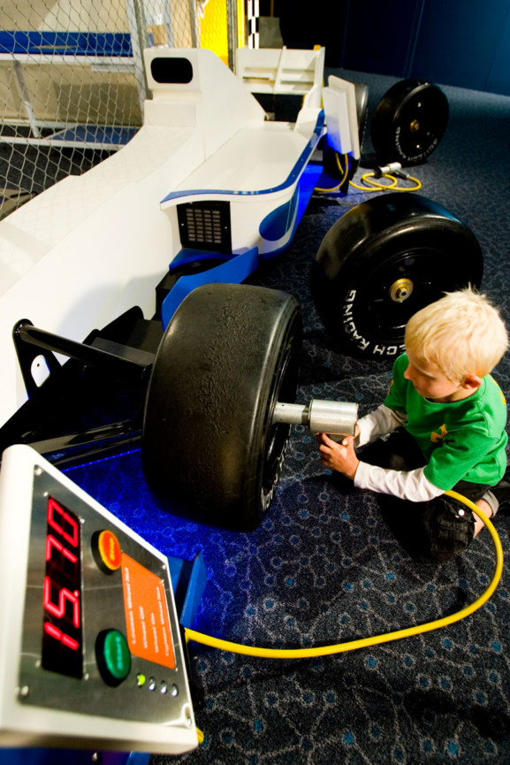 A young boy changing a tyre in the Pit Stop exhibit in Scitech's Speed Exhibition.
