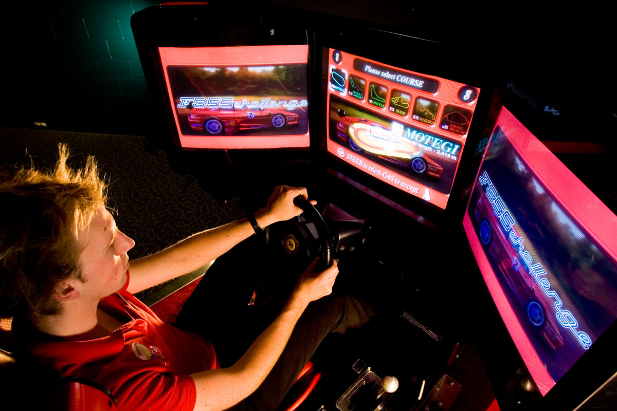 A young boy racing a car in a three screen simulator.