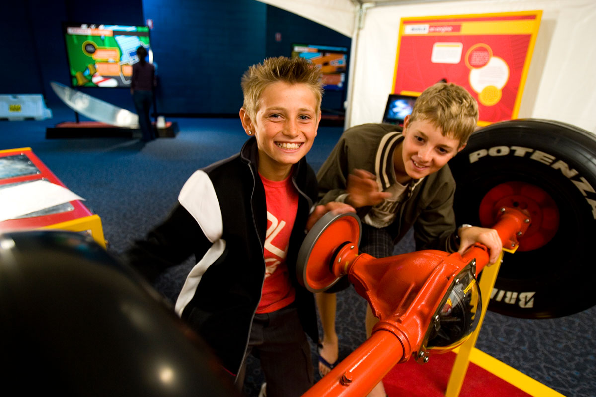 Two young boys playing with the differential of a formula one replica car.