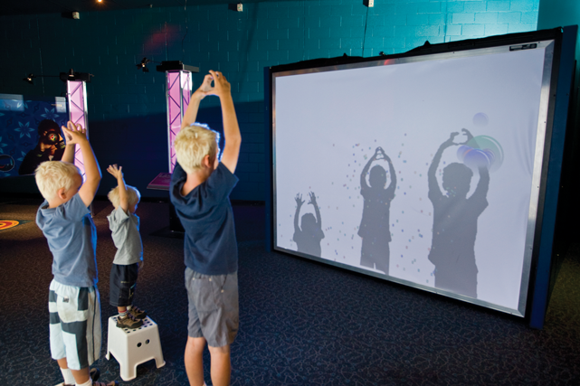 Three young boys making shadows on large white screen.